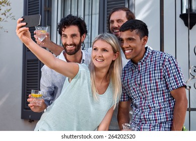 friends taking photo pictures selflie with mobile cellphone camera outdoors at garden party