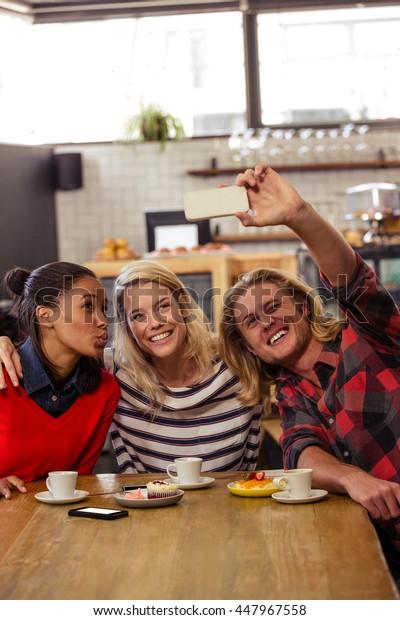 Friends taking a selfie in the cafe