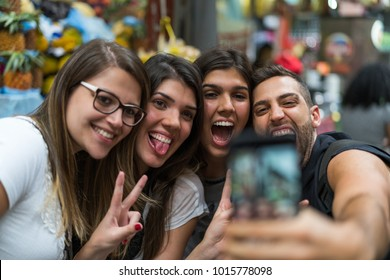 Friends taking a selfie with mobile in a Municipal Market, Sao Paulo, Brazil