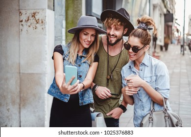 Friends taking selfie on the street and smiling. Beautiful summer day