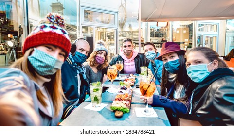 Friends taking selfie outside at cocktail bar - New normal lifestyle concept with young people having fun together at restaurant cafe covered by face masks - Vivid filter with focus on central guy  - Shutterstock ID 1834788421