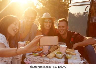 Friends taking selfie at picnic beside camper van, close up