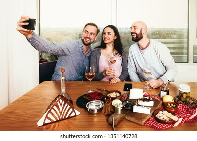 friends taking a selfie at a table with tapas food and wine celebrating friendship, life and togetherness