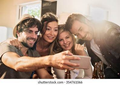 Friends taking selfies on a smartphone in a charming house. Two men and two women are holding each other arms in arms while the phone is taking the picture. Backlit shot with flare, real people.