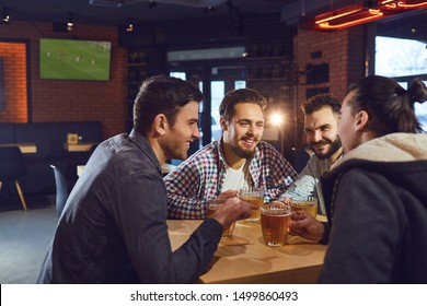 Friends talk, drink beer in a bar.