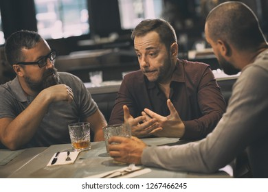 Friends talking and communicating while sitting and spending time together in bar. They drinking whiskey or scotch. Sad man in shirt having problems and men trying support their friend.