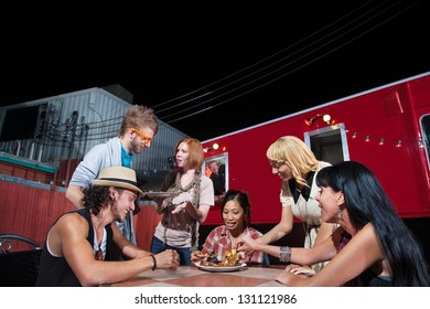 Friends talking and eating pizza near Food Truck