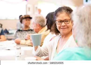 Friends talking and having coffee in a senior center