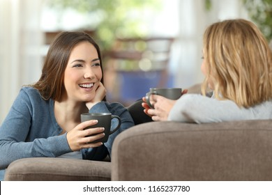 Friends talking lying on a couch in the living room at home