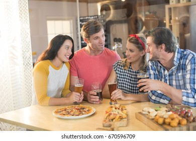 Friends talking while having beer at table in restaurant