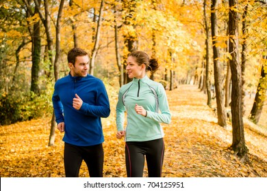 Friends talking while jogging together in beautiful autumn nature