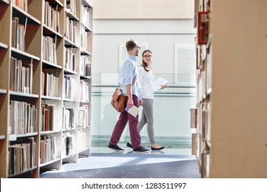 Friends talking while walking in university library