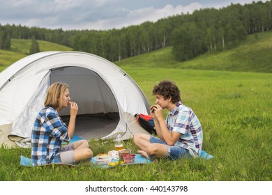 Friends teenage boy and girl eat near the tent, sitting on the green grass