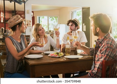 Friends in their 30s having a nice aperitif on a rustic wooden table in a lovely house. They are holding their high glasses of white wine. There are tomatoes mozzarella for starters.