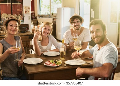 Friends in their 30's having a nice aperitif on a rustic wooden table in a lovely house. They are looking at camera and smiling in front of glasses of white wine and tomatoes mozzarella
