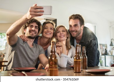 Friends in their 30's taking selfies on a smartphone in a charming house. Two men and two women are smiling while the phone is taking the picture. Backlit shot with flare, real people.