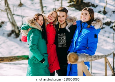 friends, three girls and one boy standing on a wooden bridge in the forest in winter