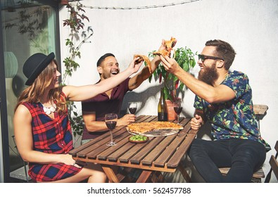 Friends toast with pizza and laugh while outside seated at patio table