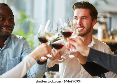 Friends toast with wine in the restaurant and celebrate birthday together