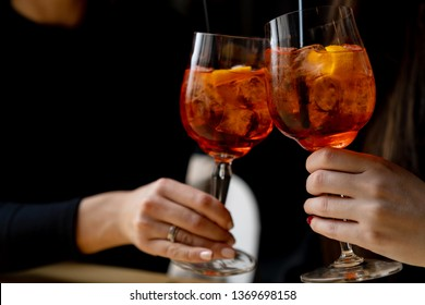Friends toasting with aperol spritz cocktails