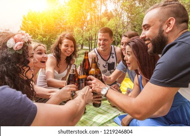 friends toasting with beer bottles enjoy their friendship during a picnic outdoor in summer. sunflares backlight from the left. focus on beer bottles.