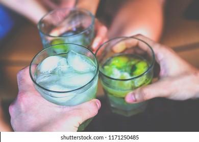 Friends toasting with Brazilian caipirinha cocktails outside