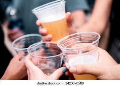 Friends toasting (cheerss) with their beer cups at an outdoor event in summer