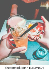 Friends toasting with cocktails (saying cheers) at a restaurant.  Focus on hands holding glasses.