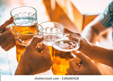 Friends toasting with glasses of light beer at the pub. Beautiful background of the Oktoberfest. A group of young people while relaxing at the bar. fine grain. Soft focus. Shallow DOF