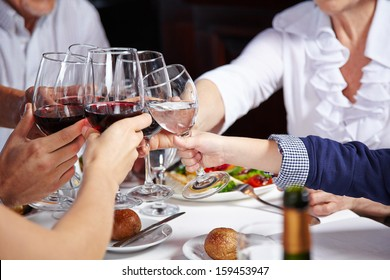 Friends toasting with glasses of red wine in a restaurant