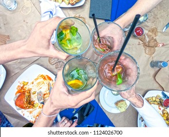 Friends toasting with margaritas and bloody mary cocktails during brunch