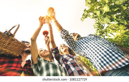 Friends toasting red wine glass up to the sky and having fun cheering at sunset backlight - Young people enjoying harvest time together at farmhouse vineyard countryside - Youth and friendship concept