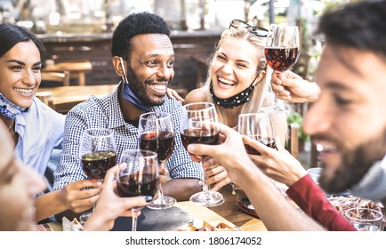 Friends toasting red wine at outdoor restaurant bar with open face mask - New normal lifestyle concept with happy people having fun together on warm filter - Focus on afroamerican guy - Shutterstock ID 1806174052