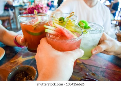 Friends toasting, saying cheers holding tropical blended fruit drinks