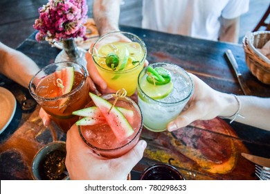 Photo of Friends toasting, saying cheers holding tropical blended fruit margaritas.  Watermelon and passionfruit drinks.