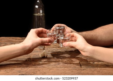 Friends toasting with shot glasses above an old wooden table black background