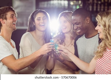 Friends toasting with shots in a pub