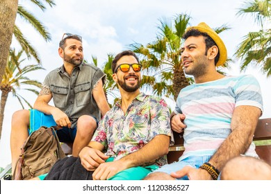 Friends together on a bench at seaside in Barcelona. Three young men with multi ethnic features relaxing and having fun, smiling and talking together. Friendship and summer concepts.
