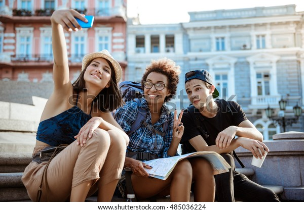 Friends travelers with backpacks smiling, making selfie, sitting near sight. Street background.