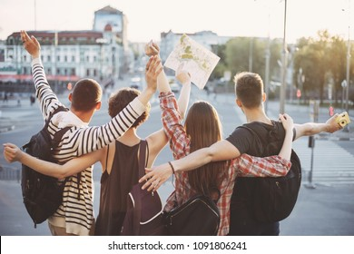 Friends traveling together. Cheerful students with backpacks rising hands at city background. People, sightseeing, vacation, holidays, adventure, friendship, togetherness