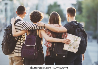 Friends traveling, togetherness, sightseeing concept. Young people with backpacks and map on city background