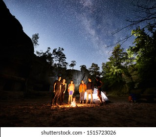 Friends travellers standing together near bonfire beside camp and glowing tourist tent at night. On background beautiful night starry sky full of stars and Milky way, mountain rocks and trees