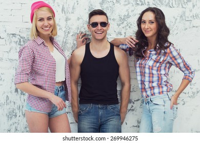 Friends two beautiful girls and handsome guy standing near a wall smile cheerfully