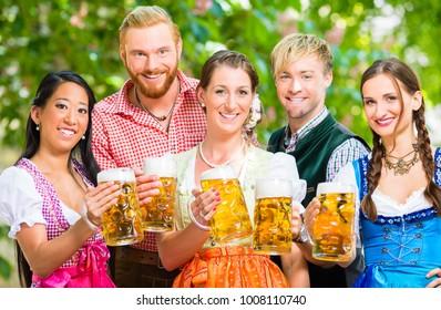 Friends, two men, three women, standing in beer garden with beer glasses