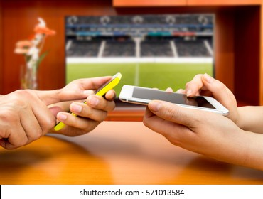 Friends using mobile phone and betting during a football or soccer match