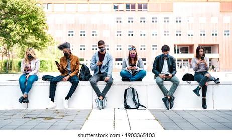 Freunde, die Smartphone mit Maske auf der dritten Covid-Welle verwenden - Sorgen und Mädchen, die Videonachrichten auf Mobiltelefonen ansehen - Studenten am Universitätscampus - Fokus auf zentrale Gesichter