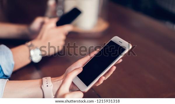 Freunde mit Smartphone, Während der Freizeit. Das Konzept der Benutzung des Telefons ist im Alltag unverzichtbar.