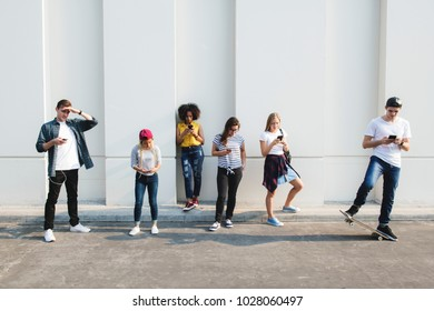 Friends using smartphones outdoors together and chilling