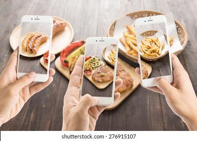 朋友使用智能手机拍摄香肠和猪排和薯条的照片。