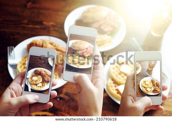 スマートフォンを使ってインスタグラム形式のフィルターで食べ物の写真を撮る友人
